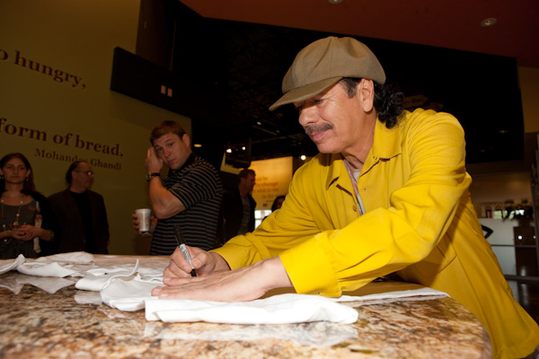 Carlos Santana signs t-shirts at Three Square Food Bank. Credit Erik Kabik/RETNA
